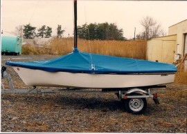 Small boat on trailer with blue boat cover
